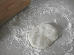 Flattening the ball of dough before rolling improves the odds that your tortillas will be round.