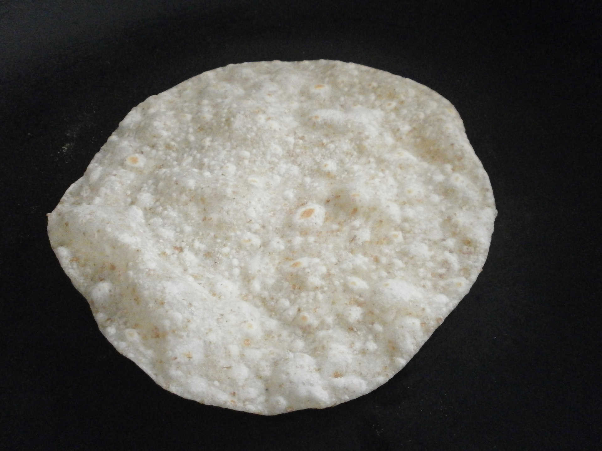 Tortilla in the skillet after flipping.