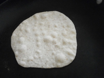 Tortilla cooking on the bottom side.