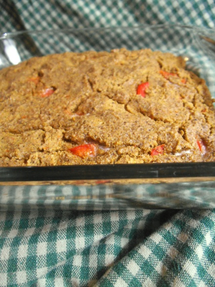A baking dish with hot cornbread flecked with sweet red pepper